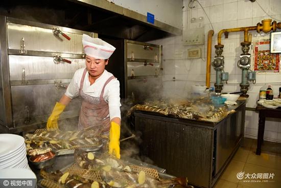 2016年10月9日,山东省日照市水芙蓉大酒店,一位厨师将蒸好的鳕鱼出锅.