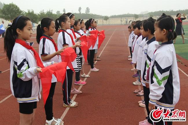 """新队员郑重地举起右拳在鲜艳的队旗下庄严宣誓:""""时刻准备着为共产主义"""