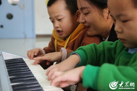 有的小孩子拉住女志愿者的手让她们教自己弹钢琴