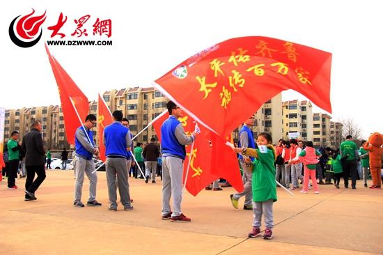 在活动启动现场,一名小朋友挥动旗帜.JPG