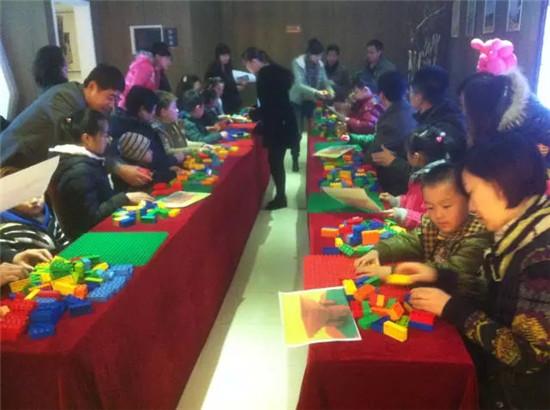 活动的签到板前,孩子们用肉嘟嘟的小手领取小小的乐高积木,拼砌自己